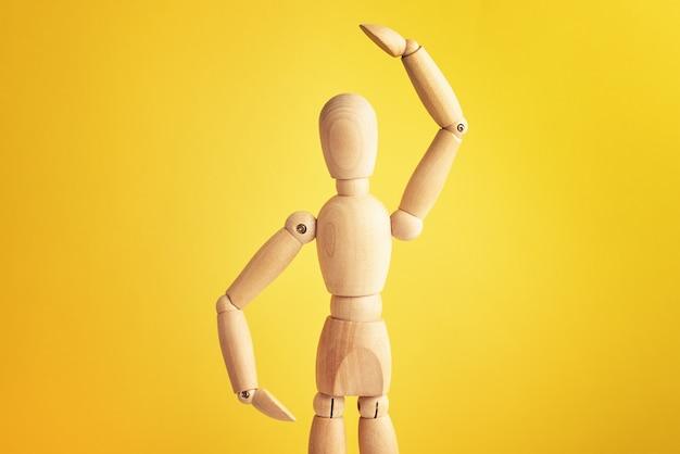 Bambola di legno con gesto su sfondo giallo manichino mostra gesto