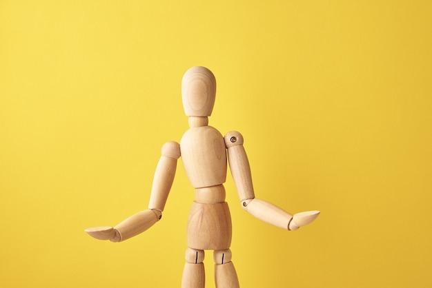 Bambola di legno su sfondo giallo