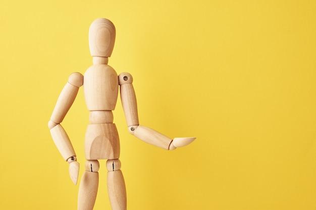 Bambola di legno su sfondo giallo Foto Premium