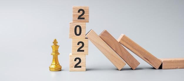 I domino in legno che cadono contro il 2022 bloccano i blocchi con la figura dorata del re degli scacchi. business, gestione del rischio, soluzione, concetto economico, assicurativo e di capodanno