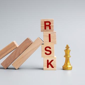 Domino di legno che cadono contro i blocchi di rischio alla figura dorata del re degli scacchi. crisi, finanza, regressione economica, assicurazioni e concept