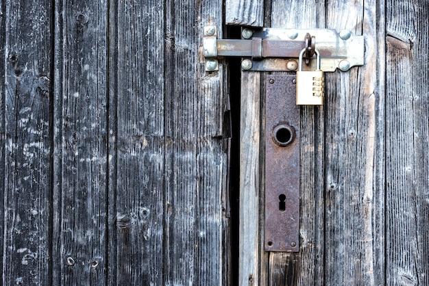 Una porta di legno chiusa con un lucchetto.
