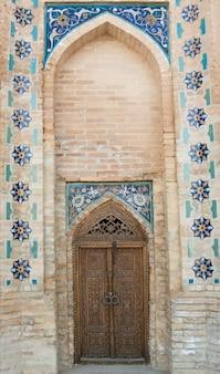 Porta di legno con l'architettura tradizionale asiatica antica dell'ornamento dell'asia centrale medievale