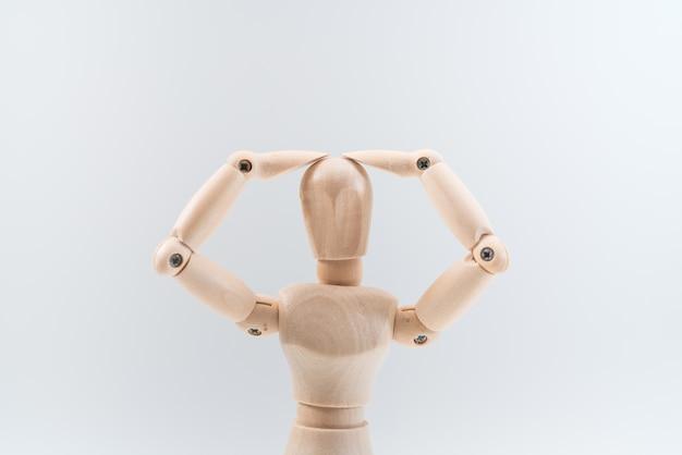 Il manichino di legno presenta con orgoglio qualcosa di invisibile, isolato