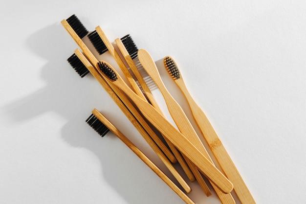 Spazzolini da denti in legno eco bambù con setole nere su sfondo bianco. stile di vita sostenibile. rifiuti zero concetto.