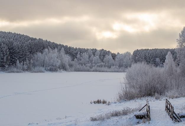 Ingresso in legno alla foresta vicino al lago ghiacciato vicino alla foresta, tutto coperto di neve