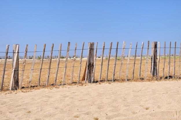 Rete fissa di legno su una spiaggia sotto il cielo blu