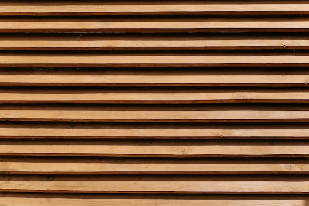 Staccionata in legno fatta di assi sottili orizzontali. fondo marrone strutturato del recinto, modello dei pannelli di legno, all'aperto