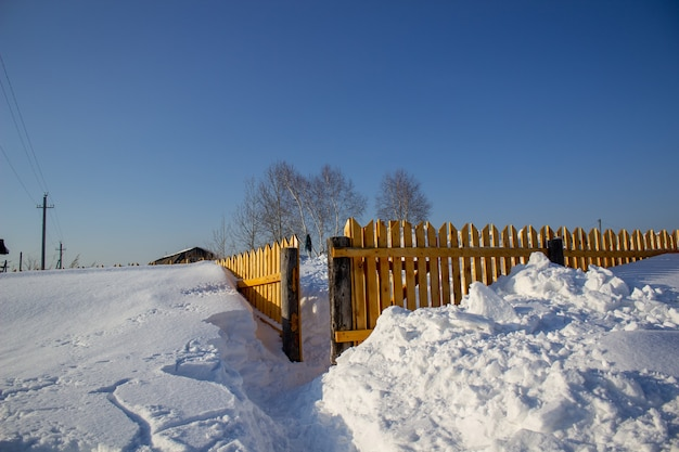Staccionata in legno nella neve. sfondo di neve.