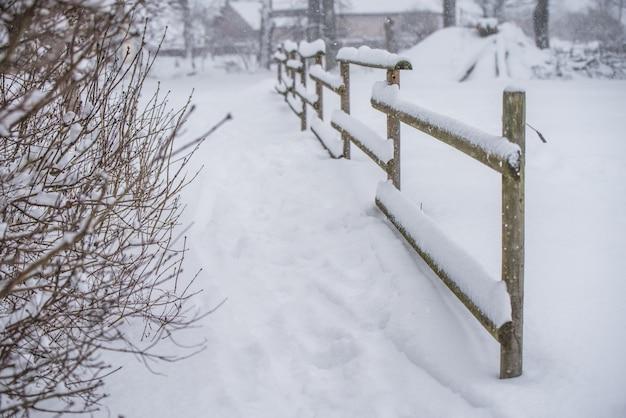 Staccionata in legno in mezzo alla neve su sfondo paese invernale.