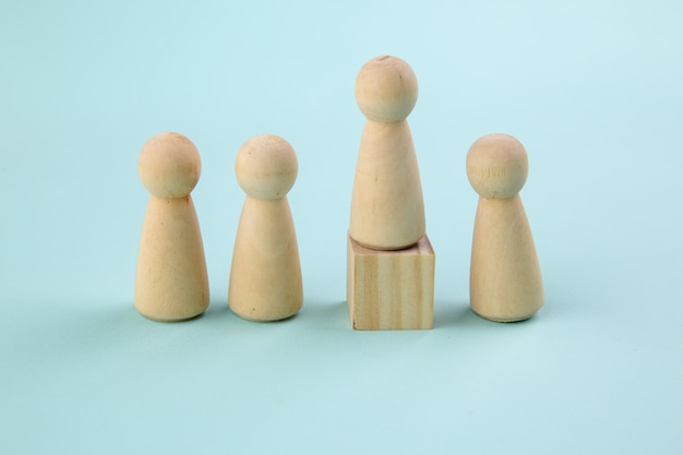 Figura in legno in piedi sulla scatola per mostrare influenza e potenziamento sul blu.