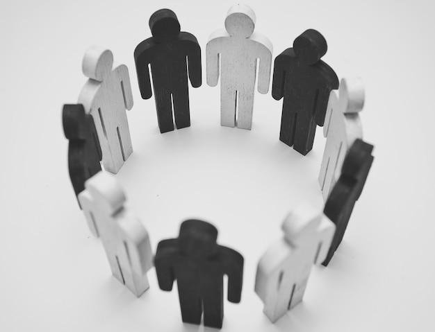 Figure in legno di persone in bianco e nero in piedi in cerchio