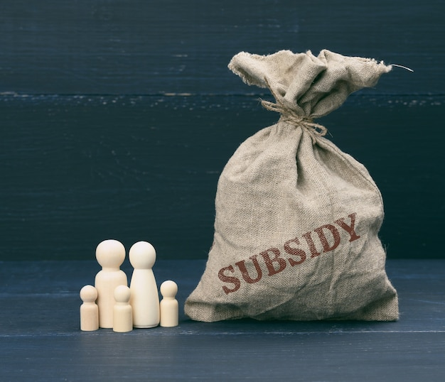 Figure in legno di ometti di famiglia e una borsa piena con la scritta sussidio su una superficie blu