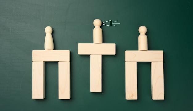 Figure di uomini in legno su un ponte fatto di sbarre, al centro c'è un negoziatore. il concetto di trovare un terreno comune, la riconciliazione degli avversari. discussione di persone. assunzione del personale