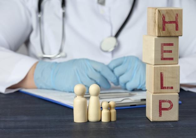 Figure in legno di uomini e la scritta aiutano su cubi di legno, dietro il tavolo siede un medico