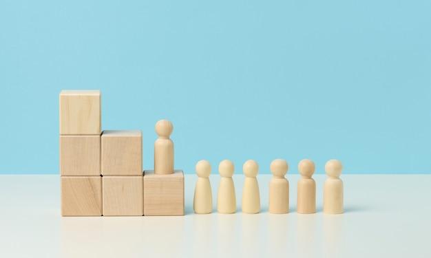 Figure in legno di uomini su una scala fatta di blocchi. il concetto di avanzamento di carriera, iniziando al lavoro, raggiungendo gli obiettivi. sfondo blu
