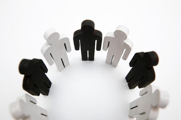 Figure in legno di colore bianco e nero persona stanno in cerchio. concetto di amicizia, lavoro di squadra e mancanza di razzismo
