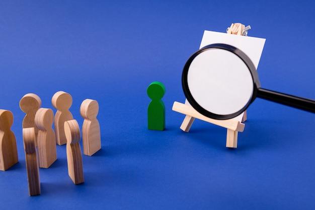Figure in legno di studenti che ascoltano la lente di ingrandimento del professore che ingrandiscono il copyspace