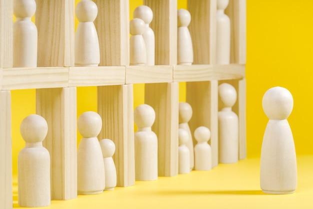 Figure in legno su superficie gialla