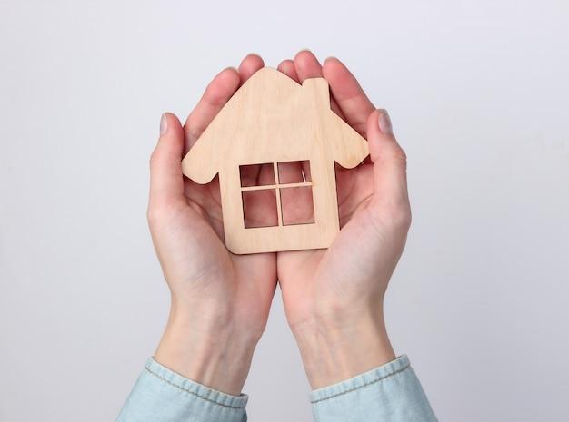 Casa di figurine di legno in mani femminili su un bianco