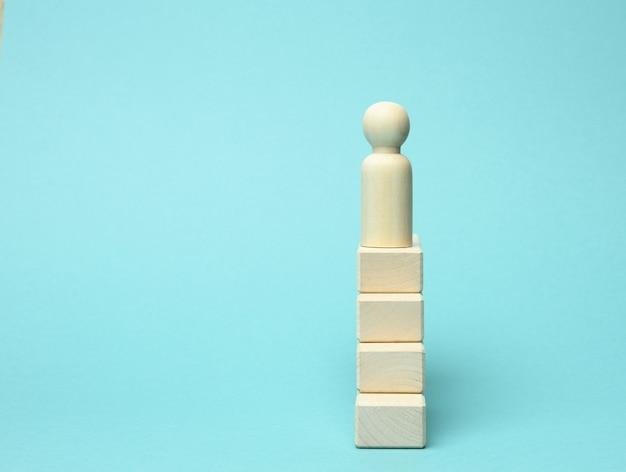 Una statuina di legno di un uomo si trova su una scala di blocchi in cima. il concetto di raggiungere gli obiettivi prefissati nel mondo degli affari, crescita professionale.