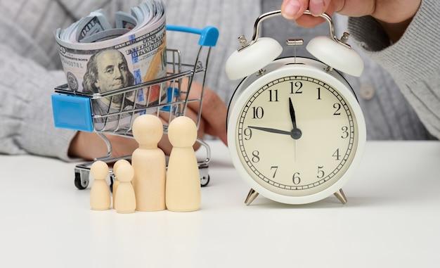 Figurine di legno di una famiglia, una mano femminile tiene una sveglia su un tavolo bianco. il concetto di tempo è denaro, pianificazione del budget. è ora di pagare i debiti