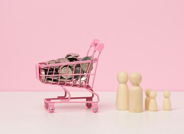 Figurine di legno di una famiglia e pile di soldi metallici, un carrello della spesa in miniatura su un tavolo bianco. concetto di controllo del bilancio familiare, risparmio