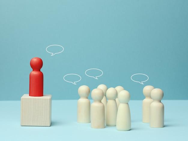 Statuine in legno di uomini. concetto di parlare in pubblico, leadership e discussione. il team si unisce attorno a un'idea, alla cooperazione