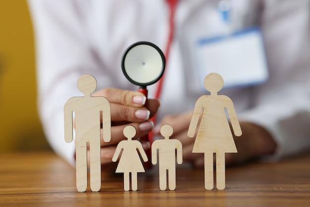 Figurine di legno di genitori e bambini in piedi sul tavolo dietro il medico seduto e tenendo lo stetoscopioth