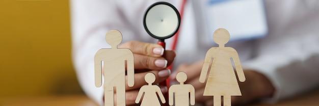 Figurine di legno di genitori e bambini in piedi sul tavolo dietro il medico seduto e con in mano uno stetoscopio
