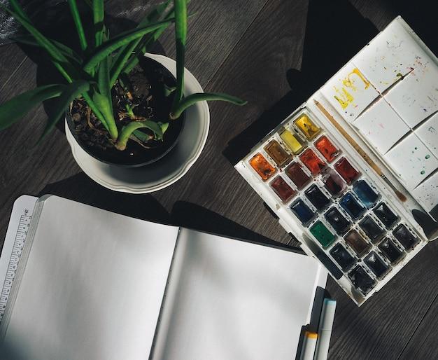 Sul pavimento di legno c'è un quaderno bianco, una pianta verde in un vaso e colori ad acquerello colorati