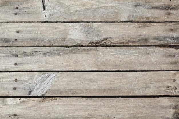 Pavimento in legno fatto di vecchie assi con nodi e crepe con chiodi arrugginiti, intemperie con sabbia. sfondo grunge