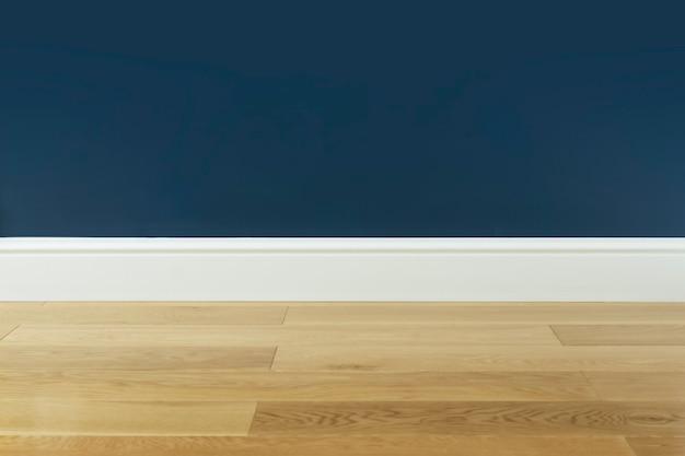 Pavimento in legno con parquet laminato e parete blu sullo sfondo della stanza vuota