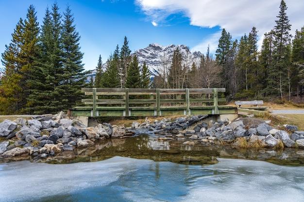 Passerella in legno nella foresta attraverso il lago ghiacciato in inverno montagna innevata in background