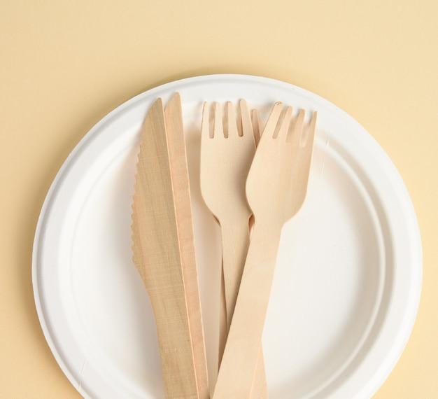 Forchetta di legno e piatto monouso marrone rotondo bianco vuoto realizzato con materiali riciclati su uno sfondo marrone, vista dall'alto. concetto di assenza di immondizia non riciclabile, rifiuto della plastica, vista dall'alto