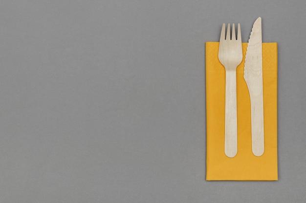 Forchetta e coltello in legno su tovagliolo arancione su sfondo grigio, vista dall'alto con spazio vuoto. stoviglie usa e getta ecologiche in materiale naturale.