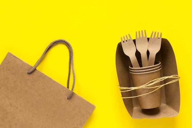 Forchette e tazze di legno nel piatto di carta del mestiere e fondo giallo della borsa
