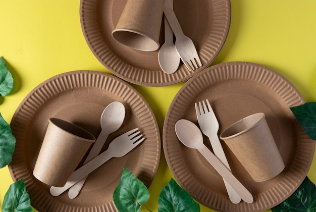 Forchette e cucchiai in legno, utensili da cucina usa e getta ecologici su sfondo giallo. rifiuti zero concetto. vista dall'alto