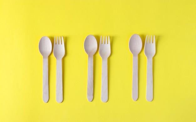 Forchette e cucchiai di legno, utensili da cucina usa e getta ecologici su superficie gialla