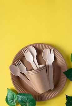Forchette e cucchiai di legno in un bicchiere di carta con piatto di carta su sfondo giallo. rifiuti zero concetto. formato verticale. vista dall'alto