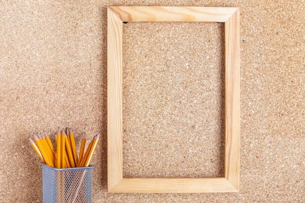 Cornice in legno su bacheca di sughero e matite
