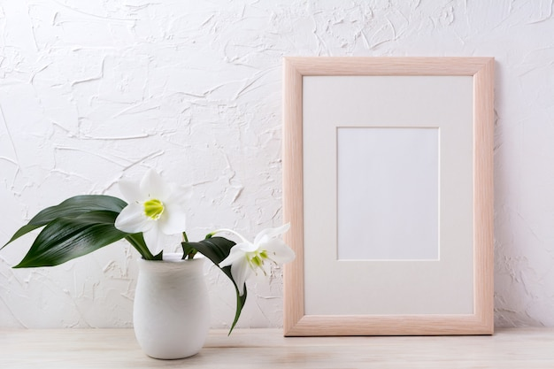 Mockup di cornice in legno con giglio bianco in vaso di fiori