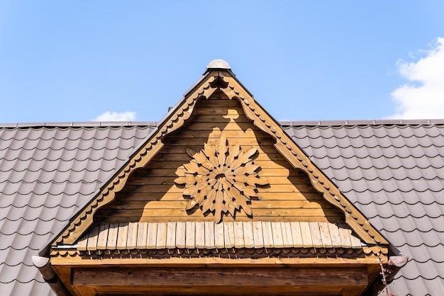 Timpano in legno e tetto in metallo contro il cielo blu