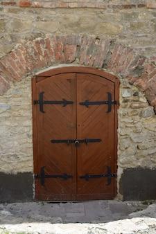 Cancelli in legno di un antico castello o fortezza medievale, rivestiti con strisce di ferro. il cancello ha un cancelletto chiuso con maniglia