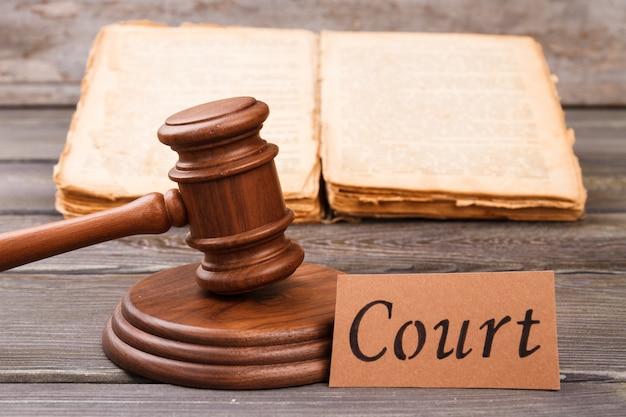 Il martelletto di legno colpisce il blocco sonoro. concetto di sentenza del tribunale. vecchio libro usurato in background.