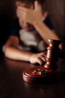 Anelli di martelletto di legno e ragazzo frustrato con orsacchiotto