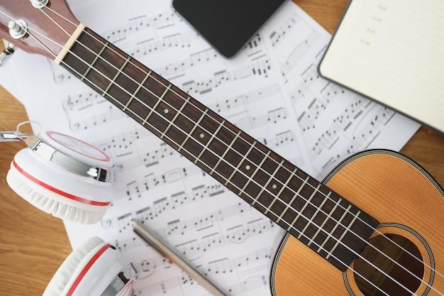Cuffie per chitarra in legno e note musicali su lezioni da tavolo sul concetto di strumento musicale