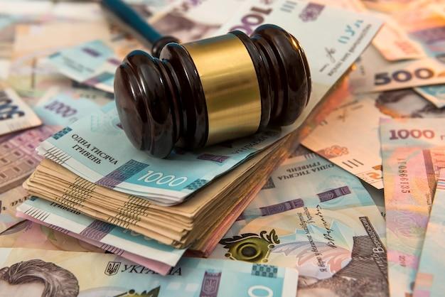 Martello di legno sui soldi dell'ucraina come sfondo. 500 e 1000 nuovi uah grivna. concetto legale o di salvataggio