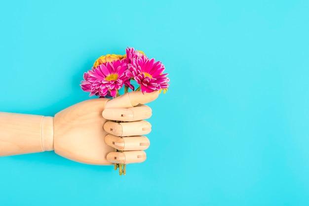 Mano in legno che tiene il mazzo di fiori primaverili