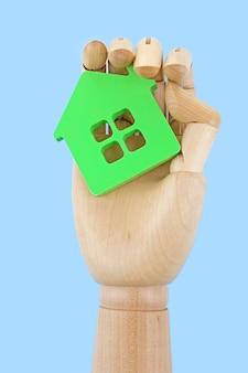 Mano in legno che tiene modello di casa su sfondo bianco